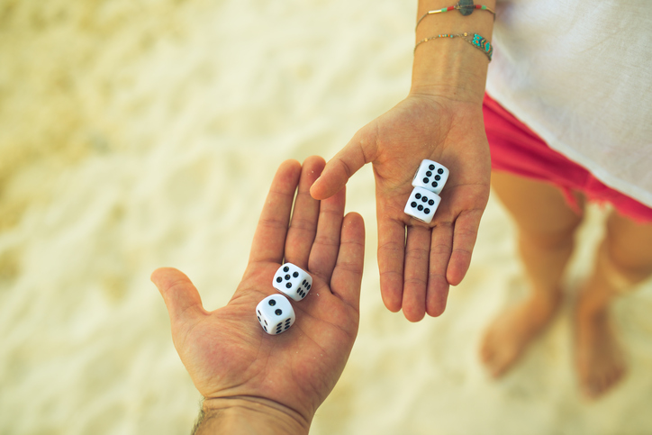 couple playing dice on the beach
